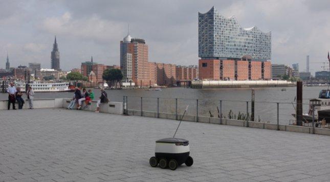 Pizza-Liefer-Roboter wird ab Sommer 2017 erstmals in Hamburg Kunden beliefern. Der Roboter passt sich laut Meldungen der Hersteller an die Geschwindigkeit dem Fußgängeraufkommen auf dem Bürgersteig an. Gegenstände und Hindernisse kann der Roboter mithilfe der On-Board-Sensoren ausweichen. (Foto: Starship Technologies, Pressefoto)