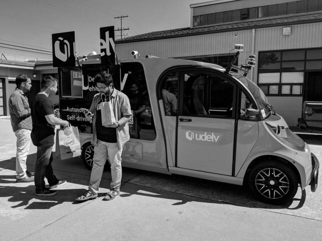 Kunden bei der Abholung von Waren aus einem Udelv-Van.